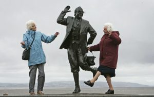two elderly ladies copying eric morecambe statue